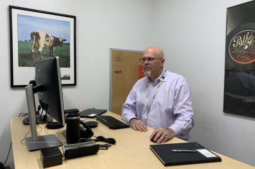 UCSC alumnus David Patmore sitting at his desk at Kioxia America