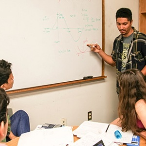 Ian Weaver (at white board) works with ACE students in a physics problem-solving session. Now a senior in astrophysics, Weaver joined the ACE Program his freshman year and has been on the student staff since he was a sophomore. (Photo by C. Lagattuta)