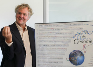 David Haussler, director of the UCSC Genomics Institute, explains a poster of the human genome sequence to visitors. (Photo by C. Lagattuta)