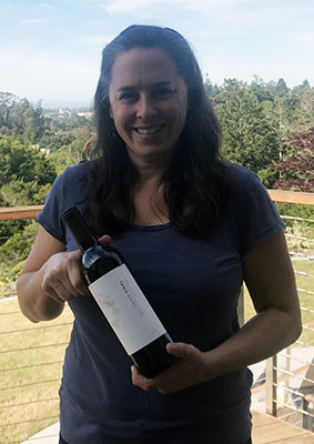 "The virologist Rebecca DuBois, UC Santa Cruz associate professor of biomolecular engineering, holding a bottle of ""Going Viral"" wine from Michael David Winery."