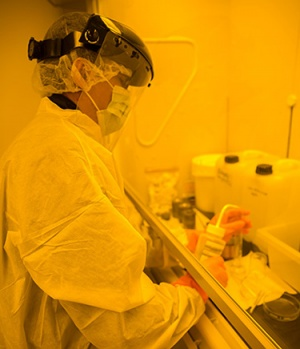 Physics graduate student Amit KC works in the clean room. (Photo by C. Lagatutta)
