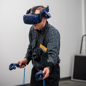 Jim Egen dons a virtual reality helmet and paddles to test ASSIST lab's stroke rehabilitation game.